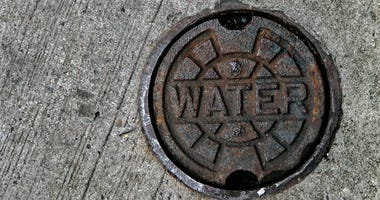 A water main manhole cover on pavement.