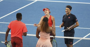 Roger Federer and Belinda Bencic of Switzerland, facing, wait at the net after winning their mixed doubles match against Frances Tiafoe and Serena Williams of the United States at the Hopman Cup in Perth, Australia, Tuesday, Jan. 1, 2019.