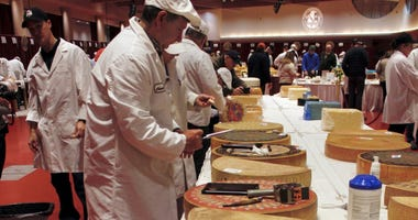 Judge Christophe Megevand inspects a wheel of Gruyere cheese at the biennial World Championship Cheese Contest, Tuesday, March 3, 2020, at the Monona Terrace Convention Center in Madison, Wis.