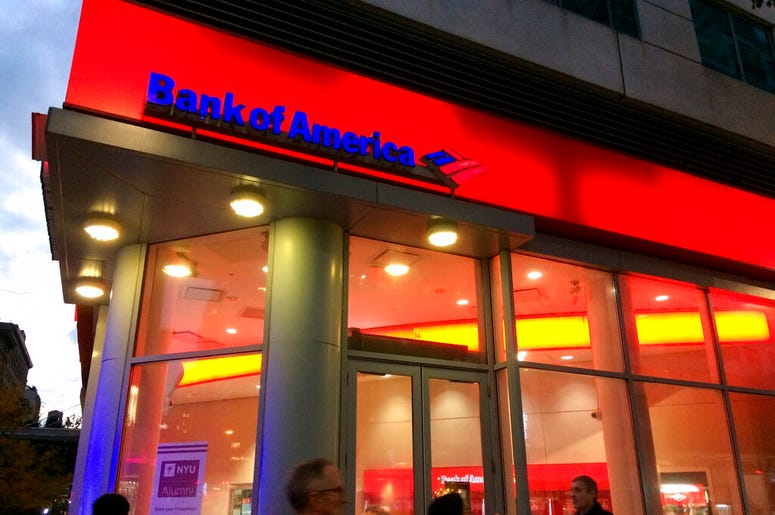FILE- In this Nov. 6, 2017, file photo, people walk by a branch office of Bank of America in New York. Bank of America is raising its starting pay to $20 an hour over a two-year period, starting with a hike next month. The company said Tuesday, April 9, 2