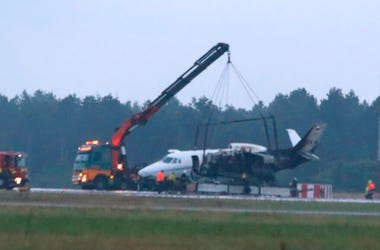 A private aircraft is recovered after it caught fire on landing at Aarhus Airport in Tirstrup, Denmark, Tuesday, Aug. 6, 2019. Flying from Oslo in Norway, the plane was believed to be carrying the manager and crew of pop singer Pink, who had given a conce