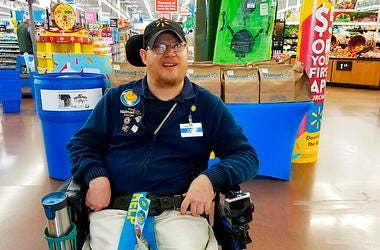 In this April 21, 2018 photo provided by Rachel Wasser, Walmart greeter John Combs works at a Walmart store in Vancouver, Wash. Combs, who has cerebral palsy, and other greeters with disabilities are threatened with job loss as Walmart transforms the gree