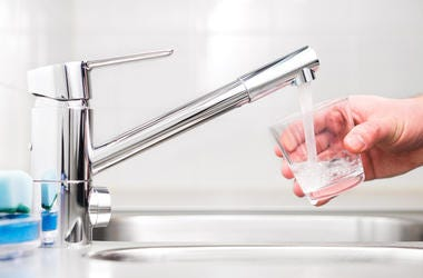 Filling glass with tap water. Modern faucet and sink.
