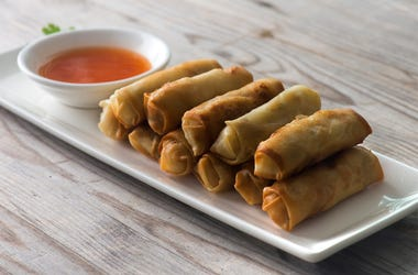 Lumpia Spring Rolls with spicy sauce on Wooden Table in Restaurant