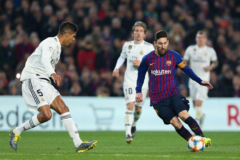 BARCELONA, SPAIN - FEBRUARY 06: Lionel Messi of FC Barcelona competes for the ball with Raphael Varane of Real Madrid CF during the Copa del Semi Final first leg match between Barcelona and Real Madrid at Nou Camp on February 06, 2019 in Barcelona, Spain.