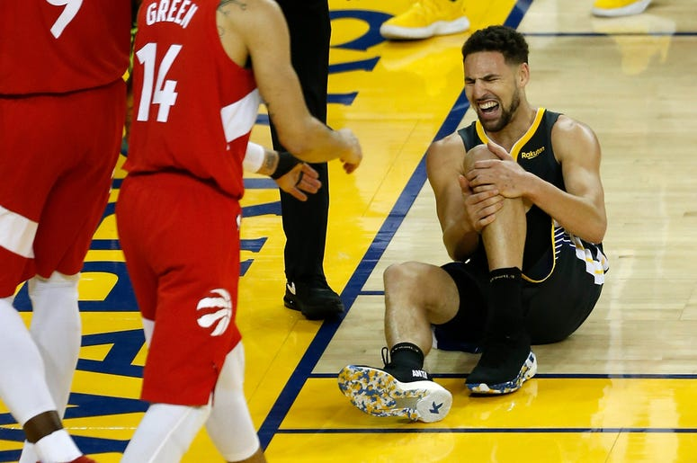 OAKLAND, CALIFORNIA - JUNE 13: Klay Thompson #11 of the Golden State Warriors reacts after hurting his leg against the Toronto Raptors in the second half during Game Six of the 2019 NBA Finals at ORACLE Arena on June 13, 2019 in Oakland, California. NOTE