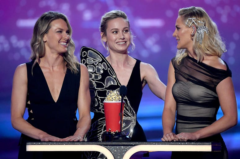 SANTA MONICA, CALIFORNIA - JUNE 15: (L-R) Brie Larson and stunt doubles Ingrid Kleinig and Joanna Bennett accept the Best Fight award for 'Captain Marvel' onstage during the 2019 MTV Movie and TV Awards at Barker Hangar on June 15, 2019 in Santa Monica, C
