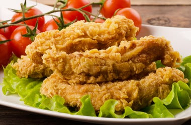 Golden fried chicken strips in breading with salad and tomatoes on a white plate (Photo credit: Aperturesound/Dreamstime)