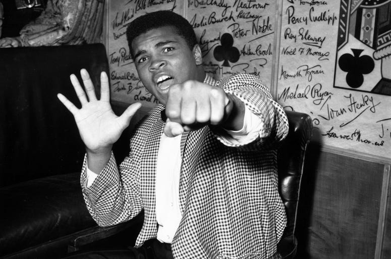27th May 1963: Supremely confident American boxer Cassius Clay holds up five fingers in a prediction of how many rounds it will take him to knock out British boxer Henry Cooper. (Photo by Kent Gavin/Keystone/Getty Images)