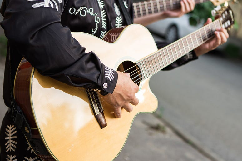 Man plays the guitar, close-up of hands. Latin American, Spanish, Mexican musician (Photo credit: Getty Images Plus )