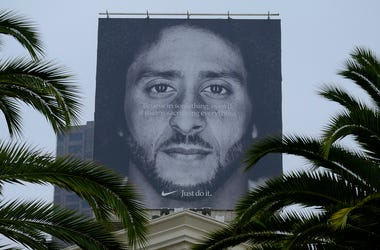 In this Sept. 5, 2018, file photo palm trees frame a large billboard on top of a Nike store that shows former San Francisco 49ers quarterback Colin Kaepernick at Union Square in San Francisco. Nike Inc. reports earnings Tuesday, Sept. 25. (AP Photo/Eric R