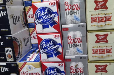 In this photo taken on Thursday, Nov. 8, 2018, cases of Pabst Blue Ribbon and Coors Light are stacked next to each other in a Milwaukee liquor store. Pabst Brewing Company and MillerCoors are heading to trial starting Monday, Nov. 12, to settle a contract