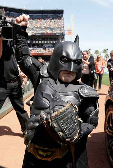 In this file photo from Tuesday, April 8, 2014, Miles Scott, dressed as Batkid, gestures after throwing the ceremonial first pitch before a baseball game between the San Francisco Giants and the Arizona Diamondbacks in San Francisco. On the five-year anni