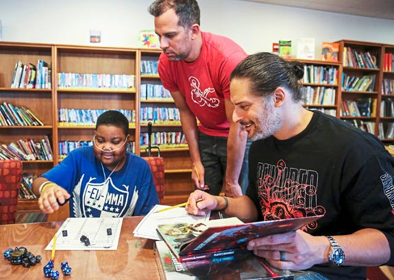 Hospital patient Yaheim Young, 15, of Penn Hills, Pa., left, Nick Manganiello, center, and his brother, Mt. Lebanon native and actor Joe Manganiello, right, count dice as they create their Dungeons and Dragons characters at UPMC Children's Hospital of Pit