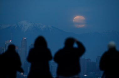 People watch the supermoon rise behind the downtown Los Angeles skyline, from Kenneth Hahn Park in Los Angeles, Sunday, Jan. 20, 2019. The year's first supermoon, when a full moon appears a little bigger and brighter thanks to its slightly closer position