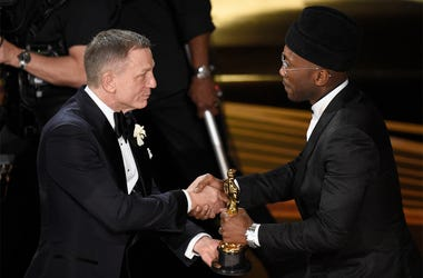 "Daniel Craig, left, presents Mahershala Ali with the award for best performance by an actor in a supporting role for ""Green Book"" at the Oscars on Sunday, Feb. 24, 2019, at the Dolby Theatre in Los Angeles. (Photo by Chris Pizzello/Invision/AP)"