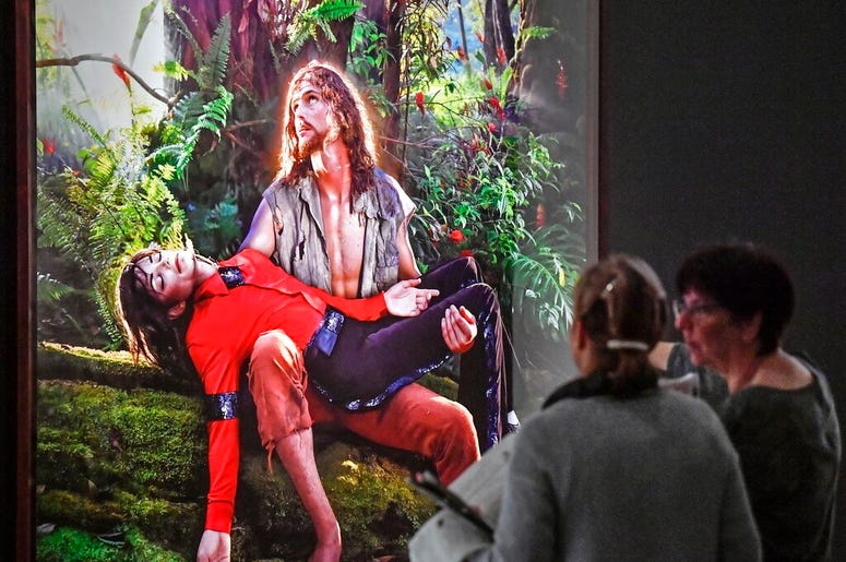Visitors talk about the picture 'American Jesus: Hold me, carry me boldly' from US artist David LaChapelle at a preview of the exhibition 'Michael Jackson: On The Wall' at the Bundeskunsthalle museum in Bonn, Germany, Thursday, March 21, 2019. The exhibit