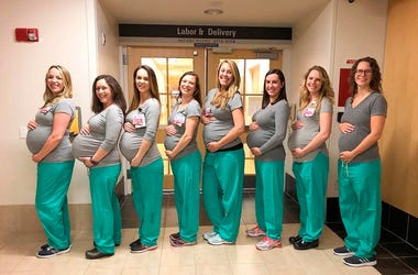 In this March 23, 2019 photo, eight labor and delivery nurses at Maine Medical Center hold up cards with their due dates in Portland, Maine. The pictured nurses, from left to right, are Erin Grenier, Rachel Stellmach, Brittney Verville, Lonnie Souci, Aman