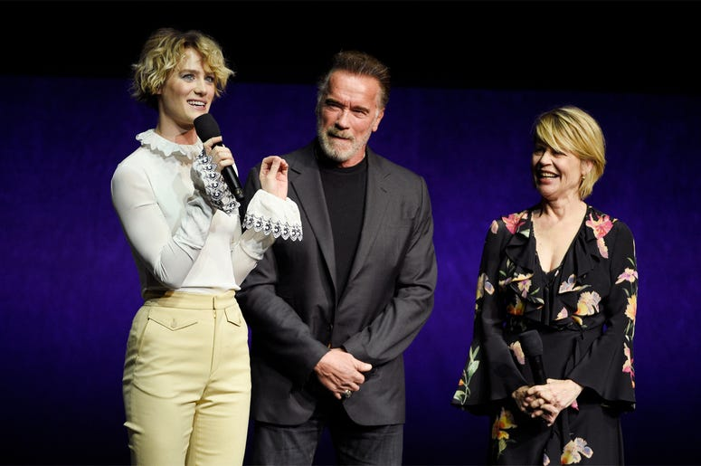 """Mackenzie Davis, left, a cast member in the upcoming film """"Terminator: Dark Fate,"""" talks about the film as fellow cast members Arnold Schwarzenegger, center, and Linda Hamilton look on during the Paramount Pictures presentation at CinemaCon 2019, the offi"""