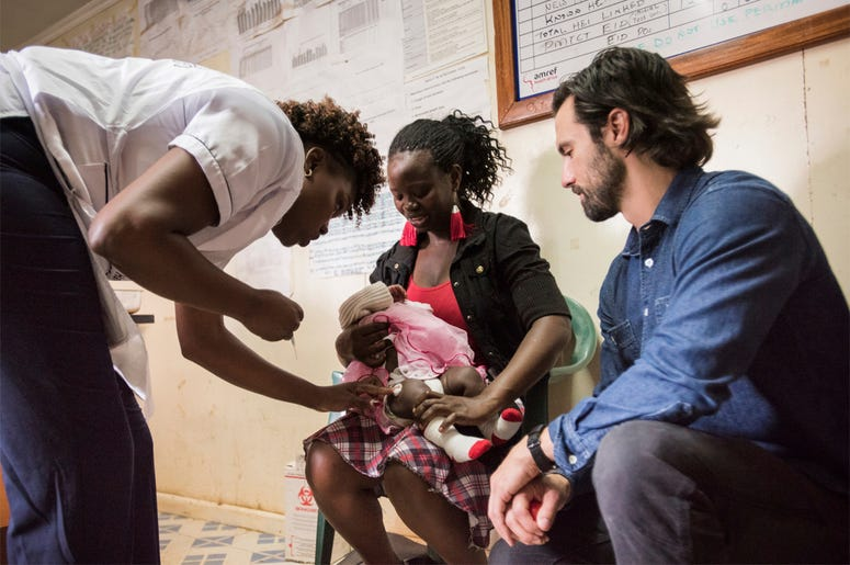 This image released by NBC shows actor Milo Ventimiglia visiting the vaccination clinic at Kibera AMREF Health Centre in Nairobi, Kenya. (Mia Collis/NBC via AP)