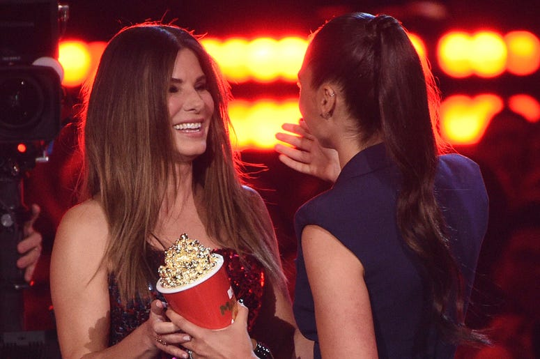 """Gal Gadot, right, presents the award for most frightened performance to Sandra Bullock for """"Bird Box"""" at the MTV Movie and TV Awards on Saturday, June 15, 2019, at the Barker Hangar in Santa Monica, Calif. (Photo by Chris Pizzello/Invision/AP)"""