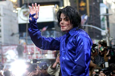 """In this Nov. 7, 2001 file photo, Michael Jackson waves to crowds gathered to see him at his first ever in-store appearance to celebrate his new album """"Invincible"""" in New York. (AP Photo/Suzanne Plunkett, File)"""