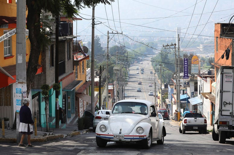 """A Volkswagen Beetle makes it to the top of a hill in a neighborhood of Mexico City known colloquially as """"Vocholandia,"""" for its love of the classic Beetle, called vochos, Tuesday, July 9, 2019. (AP Photo/Cristina Baussan)"""