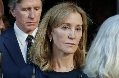 Actress Felicity Huffman leaves federal court accompanied by her brother, Moore Huffman Jr., center, after her sentencing in a nationwide college admissions bribery scandal, Friday, Sept. 13, 2019, in Boston. (AP Photo/Elise Amendola)