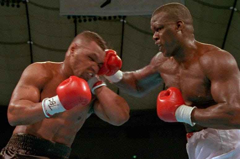 """In this Feb. 11, 1990, file photo, James """"Buster"""" Douglas, right, hits Mike Tyson with a hard right in the face during their world heavyweight title bout at the Tokyo Dome in Tokyo. (AP Photo/Sadayuki Mikami, File)"""