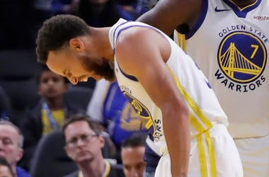 Golden State Warriors' Stephen Curry, left, grimaces as Eric Paschall (7) and Glenn Robinson III (22) watch, after Phoenix Suns' Aron Baynes fell onto Curry during the second half of an NBA basketball game Wednesday, Oct. 30, 2019, in San Francisco. Curry