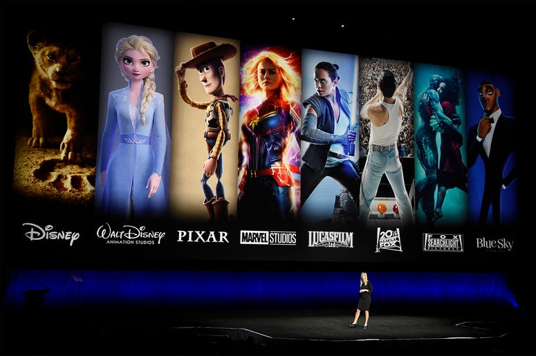 In this April 3, 2019, file photo characters from Disney and Fox movies are displayed behind Cathleen Taff, president of distribution, franchise management, business and audience insight for Walt Disney Studios during the Walt Disney Studios Motion Pictur