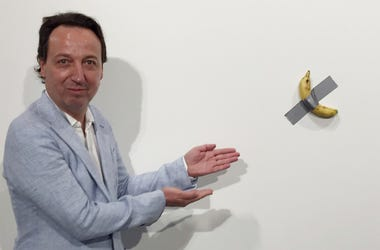 "In this Dec. 4, 2019 photo, gallery owner Emmanuel Perrotin poses next to Italian artist Maurizio Cattlelan's ""Comedian"" at the Art Basel exhibition in Miami Beach, Florida. (Siobhan Morrissey via AP)"
