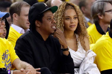 In this April 28 2018, file photo Jay-Z and Beyonce watch Game 1 of an NBA basketball second-round playoff series between the Golden State Warriors and the New Orleans Pelicans in Oakland, Calif. Police say they are pursuing more charges against a fan who