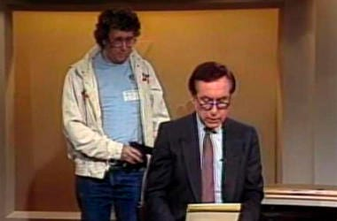 This Aug. 20, 1987, image made from video shows an intruder with a gun, as journalist David Horowitz is taken hostage during a live broadcast of Channel 4 Los Angeles. Horowitz remained calm and read the gunman's statements on camera, but the station had
