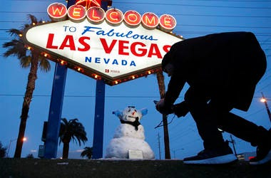 """A man, who declined to give his name, takes a picture of a small snowman at the """"Welcome to Fabulous Las Vegas"""" sign along the Las Vegas Strip, Thursday, Feb. 21, 2019, in Las Vegas. (AP Photo/John Locher)"""