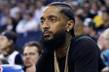In this March 29, 2018, file photo, rapper Nipsey Hussle watches an NBA basketball game between the Golden State Warriors and the Milwaukee Bucks in Oakland, Calif.