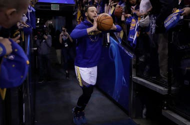 In this Sunday, April 7, 2019, photo, Golden State Warriors' Stephen Curry shoots from the players' entrance tunnel prior to the team's NBA basketball game against the Los Angeles Clippers in Oakland. (AP Photo/Ben Margot)