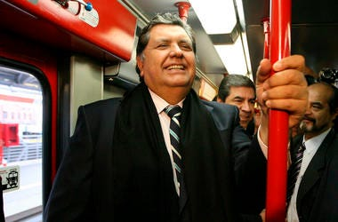 In this July 11, 2011 file photo, Peru's outgoing President Alan García, left center, rides the new Line 1 electrical train system, in Lima, Peru. (AP Photo/Martin Mejia, File)