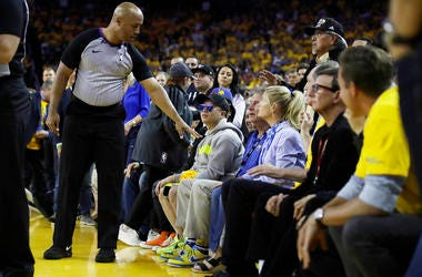 Referee Marc Davis gestures toward Golden State Warriors investor Mark Stevens
