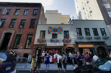 People gather near the Stonewall Inn Thursday, June 27, 2019, in New York. (AP Photo/Frank Franklin II)