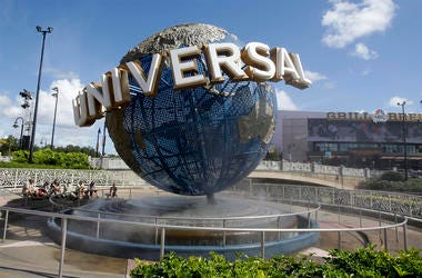 In this Oct. 22, 2015,file photo, park guests relax and cool off with a water mist under the globe at Universal Studios City Walk in Orlando, Florida. (AP Photo/John Raoux, File)