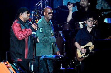 """Musician Stevie Wonder, left, is escorted by comedian Dave Chappelle during the """"Gem City Shine,"""" event in the Oregon District in Dayton, Ohio, Sunday, Aug. 25, 2019. (Marshall Gorby/Dayton Daily News via AP)"""