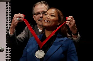 Music artist and actress Queen Latifah receives the W.E.B. Dubois Medal for her contributions to black history and culture from Glenn H. Hutchins during ceremonies at Harvard University, Tuesday, Oct. 22, 2019, in Cambridge, Mass. (AP Photo/Elise Amendola