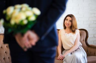 Man hiding flowers from his girlfriend