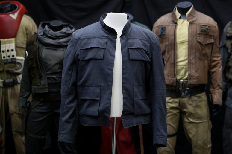 7/30/2018 - Han Solo's jacket, as worn by Harrison Ford in Star Wars: The Empire Strikes Back (estimate £500,000 - £1,000,0000) on display in front of costumes from Rogue One: A Star Wars story, on display at the Prop Store head office near Ri