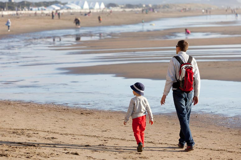 Family of father and his son walking together at the beach in California. (Photo credit: Getty Images)