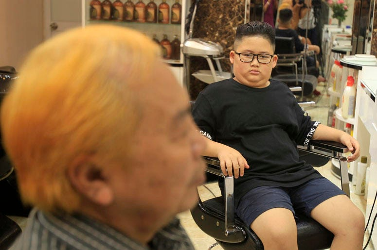Le Phuc Hai, 66, left, and To Gia Huy, 9, have Trump and Kim haircuts in Hanoi, Vietnam, on Tuesday, Feb. 19, 2019. U.S. President Donald Trump and North Korean leader Kim Jong Un have become the latest style icons in Hanoi, a week before their second sum