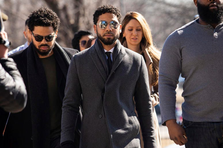 """""""Empire"""" actor Jussie Smollett, center, arrives at Leighton Criminal Court Building for a hearing to discuss whether cameras will be allowed in the courtroom during his disorderly conduct case on Tuesday, March 12, 2019, in Chicago. (Ashlee Rezin/Chicago"""
