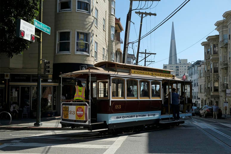 A cable car turns onto Washington Street with the Transamerica Pyramid in the background Wednesday, Sept. 11, 2019, in San Francisco. (AP Photo/Eric Risberg)