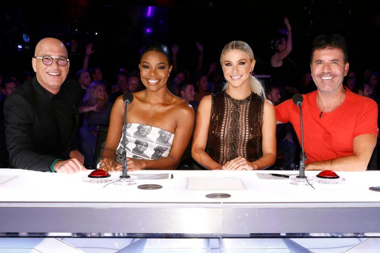 """This image released by NBC shows celebrity judges, from left, Howie Mandel, Gabrielle Union, Julianne Hough, Simon Cowell on the set of """"America's Got Talent,"""" in Los Angeles. (Trae Patton/NBC via AP)"""